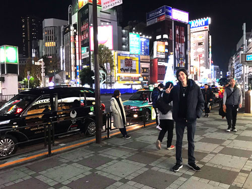 Man standing in front of Ikebukuro station at night in Tokyo, Japan
