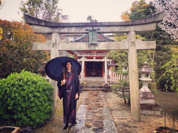 Man wearing a kimono in front of a shrine in Japan
