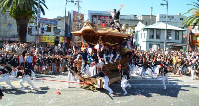Men pulling a heavy float during the Danjiri Matsuri festival in Osaka, Japan
