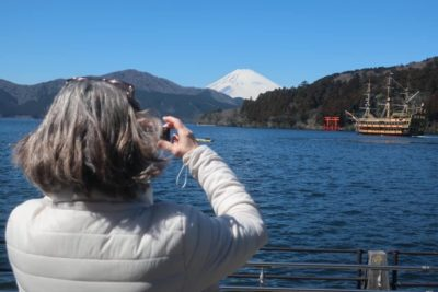 Woman taking a picture of Mt Fuji on Lake Ashi in Hakone, Japan