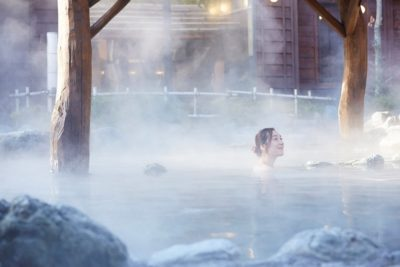 Woman in outdoor onsen hot spring in Kusatsu, Japan