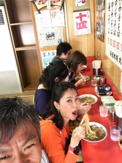 Tourists eating ramen noodles in a noodle bar in Japan