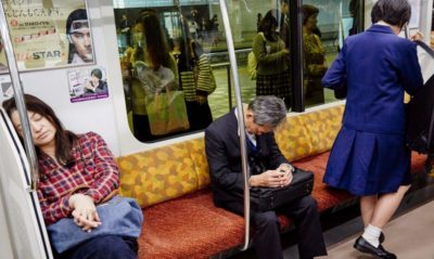 A man in a suit sleeps in a train in Japan