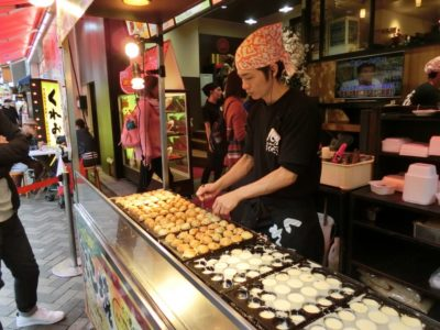 A chef making takoyaki in Dotonbori, Osaka, Japan