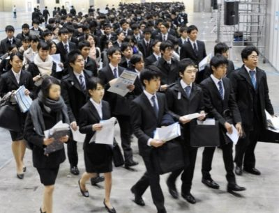 Dozens of young Japanese job seekers wearing suits