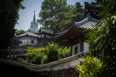 A temple in Hirado, Japan with the St. Francis Xavier Memorial Church in the background