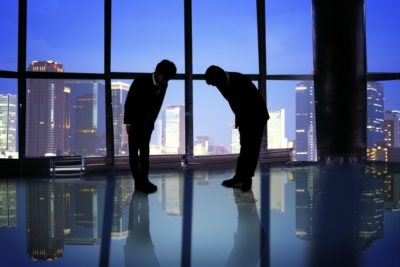 Two Japanese men bowing in an office