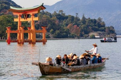 Torii gate of Miyajima during high tide with a boat next to it