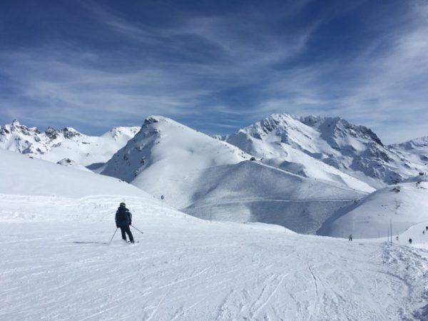Lone skieer on a wide piste