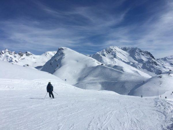 Lone skieer on a wide piste