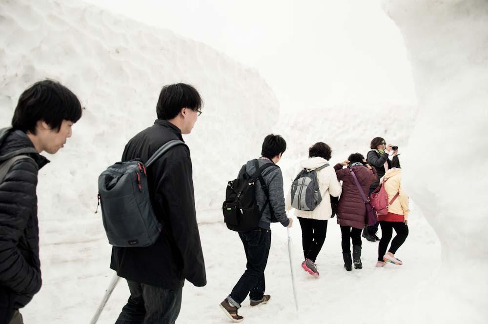 people walking next to high snow wall in kurobe japan